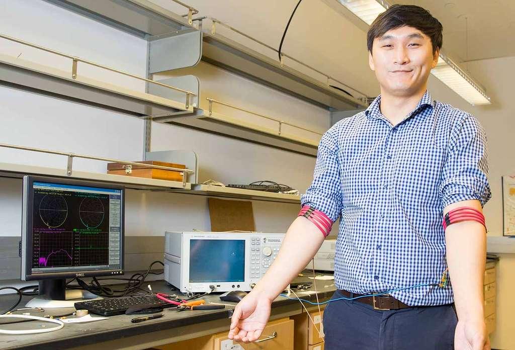 Cet ingénieur de l'université de Californie à San Diego porte deux prototypes de bracelets conçus à partir d'un fil de cuivre enrobé de PVC. Pour fonctionner, il faut que la bobine soit enroulée autour d'un membre afin que les champs magnétiques puissent se propager. © UC San Diego