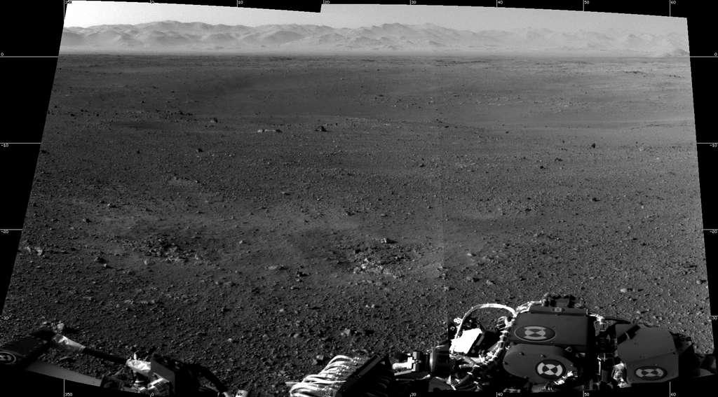 La première image en haute résolution du site d'atterrissage de Curiosity, juxtaposition de deux photographies prises avec les « navcams », caméras de navigation, installées en haut du mât, lequel a été correctement redressé. À l'horizon se dresse le rebord du cratère Gale, dont l'aspect irrégulier est dû à la longue érosion qu'il a subie. Les deux dépressions visibles devant le robot ont été creusées par le souffle des rétrofusées de la grue aéroportée. © Nasa/JPL-Caltech