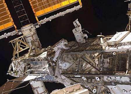 Deuxième sortie. Heidemarie Stefanyshyn-Piper (gauche) et Shane Kimbrough, spécialistes de mission, au travail sur le SARJ. Comparez la taille des astronautes par rapport à cette (petite) partie de la station et au diamètre du dispositif rotatif. Cliquer pour agrandir. Crédit Nasa