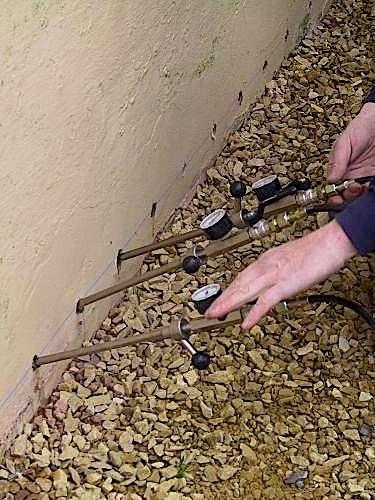 Pour réaliser une barrière chimique contre l'humidité, selon le produit, l'injection se fait sous une pression donnée (basse) ou par gravité à l'aide de réservoirs individuels remplis au fur et à mesure. © dakdurieux.be