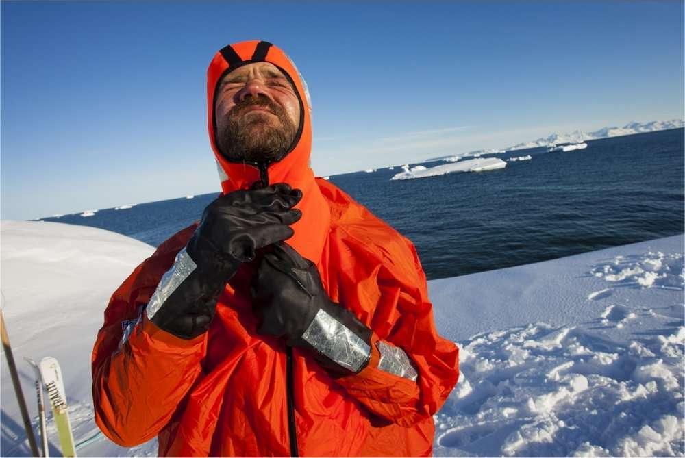 Alan Le Tressoler, sur la banquise groenlandaise, enfile une combinaison étanche avant de traverser un chenal d'eau libre. © Pôle Nord 2012