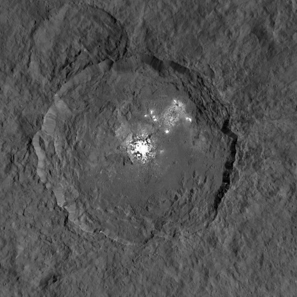 Une des vues les plus détaillées du cratère Occator (90 km de diamètre), prises par la sonde Dawn, où figure l'ensemble de taches brillantes le plus remarquable de Cérès. Des panaches ont été observés lorsque la région est exposée au Soleil. © Nasa, JPL-Caltech, UCLA, MPS, DLR, IDA