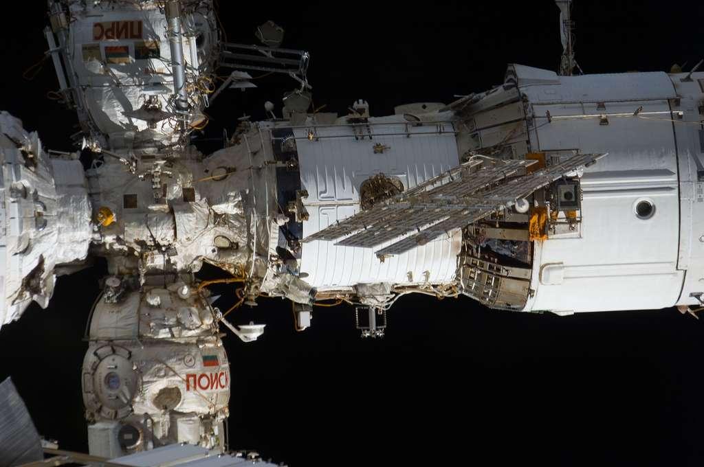 Le module russe Zvezda photographié en juillet 2011 depuis la navette spatiale lors de sa dernière mission (STS-135). En haut à gauche, se trouve le module Pirs, port d'amarrage sur lequel peuvent s'amarrer les véhicules russes Soyuz et Progress, et qui peut servir de sas de sortie dans l'espace. En bas, se trouve le module Poisk (Mini-Research Module-2), où des expériences scientifiques russes sont menées, et qui peut aussi servir de sas de sortie et de port d'amarrage pour les véhicules russes. © Nasa