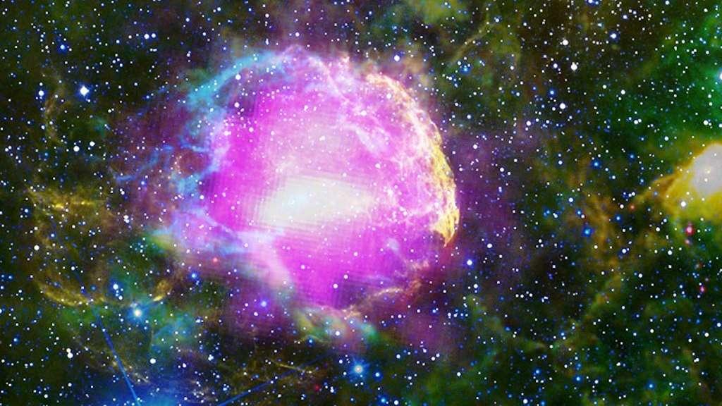 Cette image composite, réalisée avec des photographies prises par plusieurs télescopes, montre le reste de supernova IC 443, situé à 5.000 années-lumière du Soleil dans la constellation des Gémeaux. On l'appelle parfois la nébuleuse de la Méduse. Les émissions de rayons gamma observées par Fermi sont ici montrées en magenta et celles dans le visible en jaune. Les autres couleurs correspondent à des émissions dans l'infrarouge. © NASA/DOE/Fermi LAT Collaboration, NOAO/AURA/NSF, JPL-Caltech/UC