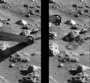 Prélèvement d'un peu de sol martien par le bras mécanique pour analyse. Crédit Nasa