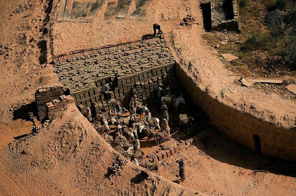 Briqueterie à l'est d'Agra, Uttar Pradesh, Inde (27°04' N - 78°53' E). De nombreuses briqueteries se sont développées dans la périphérie d'Agra, ville du nord de l'Inde. Le travail non qualifié dans ce type de fabrique est souvent exécuté par des enfants, main-d'œuvre habile et docile. En Asie, 19 % des enfants entre 5 ans et 14 ans travaillent, souvent dans des conditions dangereuses (dans les mines, au contact de machines ou de produits nocifs). © Yann Arthus-Bertrand - Tous droits réservés