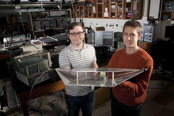 Deux étudiants en génie électrique de l'université Duke, Alexander Katko (à gauche) et Allen Hawkes, montrent un guide d'onde contenant une seule cellule en métamatériaux, qui fournit assez d'énergie pour alimenter une Led verte. © Université Duke