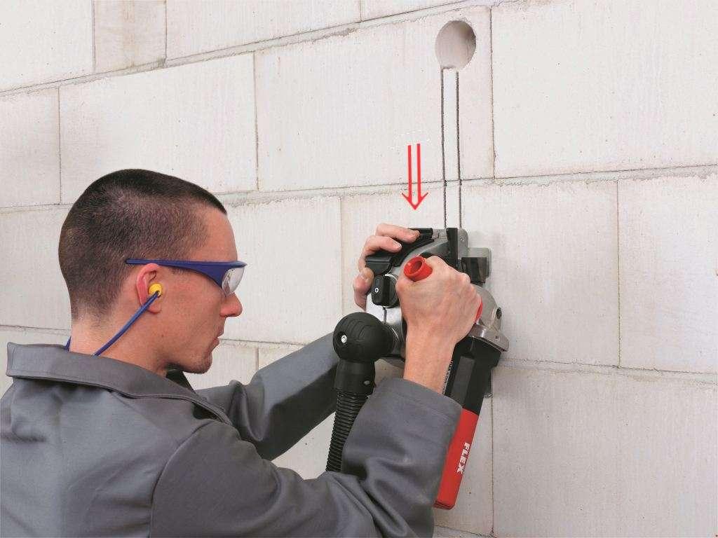 La rainureuse entaille le mur en descendant. Il est utile de la raccorder à un aspirateur d'atelier et de prévoir des accessoires de protection adaptés : masque à poussière, lunettes, casque antibruit, gants de chantier. © Flex