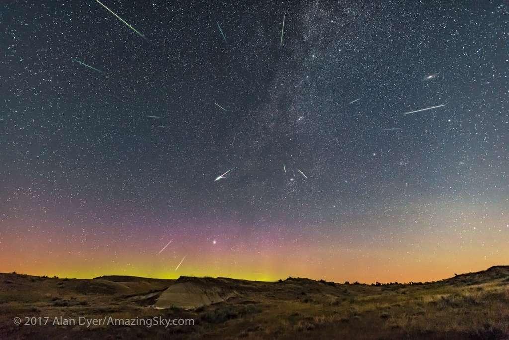 Photo composite prise dans la nuit du 12 au 13 août 2017 dans le Dinosaur Provincial Park, en Alberta au Canada. Le radiant des Perséides est bien visible, en direction de Persée et de la Voie lactée. En haut à droite, on aperçoit le disque laiteux de la galaxie d'Andromède. En bas, à gauche, une délicate aurore boréale embrase l'horizon. © 2017 Alan Dyer, AmazingSky.com