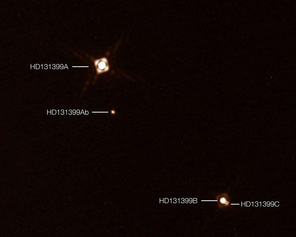 Sur cette image composite annotée figure l'exoplanète HD 131399Ab récemment découverte au sein du système triple d'étoiles HD 131399. Cette image a été constituée à partir de deux images distinctes de Sphere représentant, pour l'une les trois étoiles et pour l'autre la planète de faible luminosité. Sur cette image, la planète apparaît plus brillante qu'elle ne l'est en réalité, comparée aux étoiles. © ESO, K. Wagner et al.