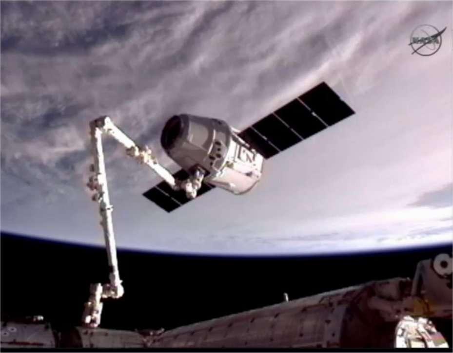 La capsule Dragon au bout du bras robotique, une vingtaine de minutes après avoir été agrippée, vue de l'ISS. Au-dessus, la Terre. © Nasa