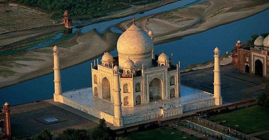 """Le Taj Mahal à Agra, Uttar Pradesh, Inde (27°10' N - 78°03' E).Construit entre 1632 et 1653 à la demande de l'empereur moghol Shah Jahan, le Taj Mahal est dédié à son épouse, Mumtaz Mahal (l'"""" élue du palais """"), morte en mettant au monde leur quatorzième enfant. Du haut de ses 74 m, il surplombe la rivière Yamuna à Agra, au nord du pays. Orné de fines sculptures et incrustations de pierres semi-précieuses représentant des versets coraniques, des motifs floraux et géométriques, ce mausolée de marbre blanc est l'œuvre d'une trentaine d'architectes et 20.000 ouvriers. © Yann Arthus-Bertrand - Tous droits réservés"""