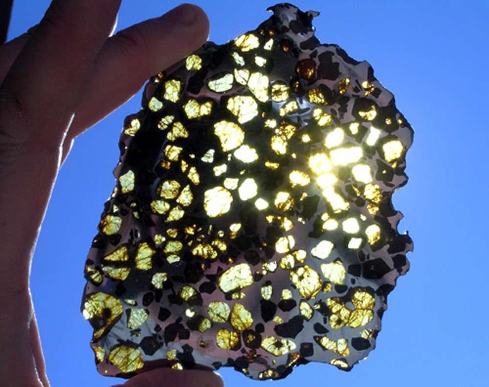 Ci-dessus, on observe une lame de 109,7 g., extraite de la pallasite d'Imilac, une météorite découverte en 1822 dans le désert d'Atacama au Chili. Les cristaux d'olivine sont transparents tandis que l'alliage de fer et de nickel, totalement opaque, présente des reflets gris-bleuté. © Michael Farmer, meteorite hunter, 2012