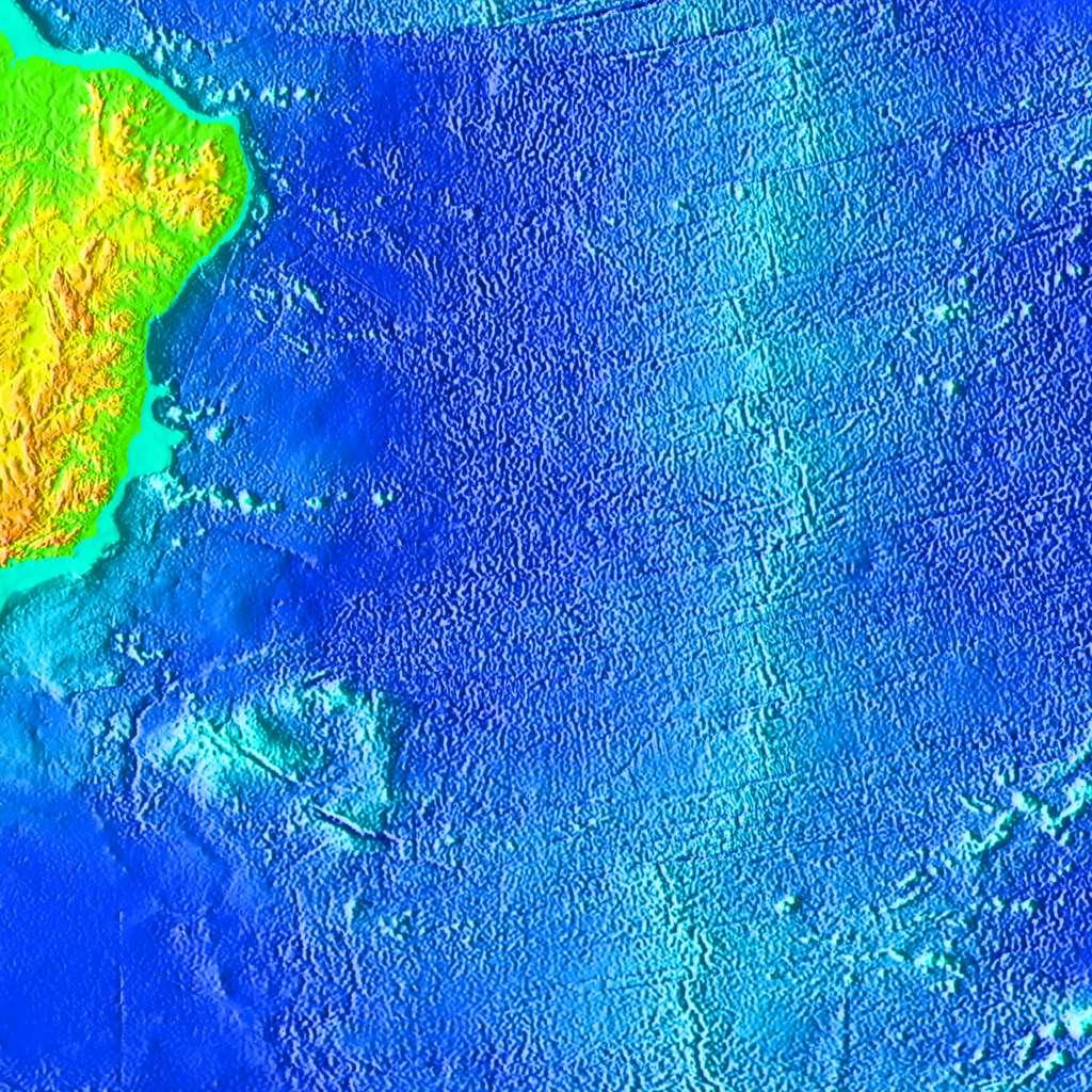 Bathymétrie du plancher océanique dans l'océan sud Atlantique. La dorsale est visible (linéation nord-sud) et intensément découpée par les failles transformantes (linéations est-ouest) qui se propagent dans la croûte océanique sur des milliers de kilomètres. © Etopo2, NOAA