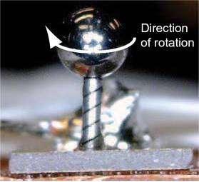 Le prototype vu de près (cliquer sur l'image pour l'agrandir). La tige rainurée hélicoïdalement est le stator et mesure un peu plus de 1 millimètre de hauteur pour 250 microns de diamètre. Il peut tourner sur lui-même et porte une sphère visualisant la rotation. L'ensemble repose sur l'élément piézo-électrique (de couleur grise). © J. Friends et al.