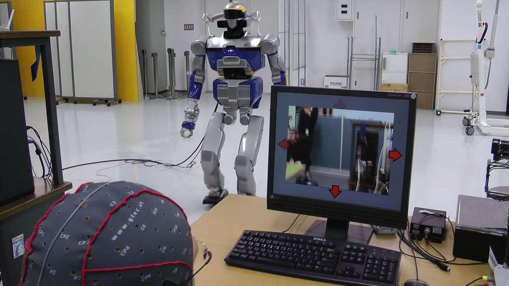Au premier plan, on distingue l'opérateur humain équipé d'un casque EEG. L'écran affiche la vue subjective retransmise par le robot équipé de caméras. En concentrant son attention sur l'une des flèches rouges de direction qui se superposent en réalité augmentée et auxquelles sont associées des actions, la personne indique son intention au logiciel qui détecte les signaux neuronaux correspondants et envoie la commande au robot. © CNRS-AIST JRL