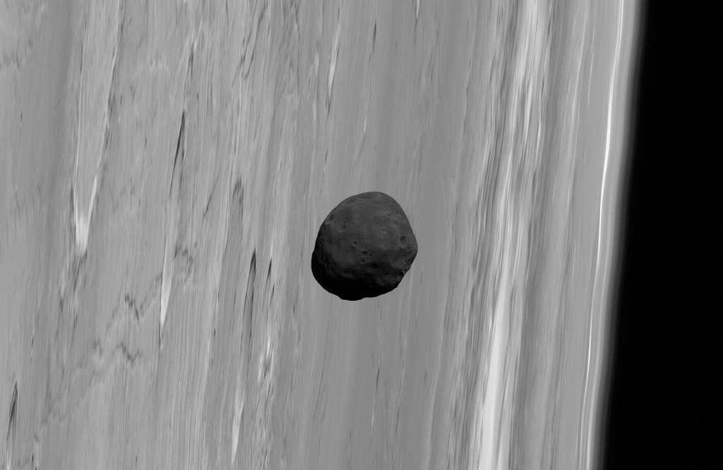 Phobos, un sombre satellite qui passe devant Mars. Il ressemble, mais c'est contestable et contesté, aux météorites à chondrites carbonées qui proviennent des régions les plus éloignées de la ceinture d'astéroïdes. Ce qui laisse à penser qu'il ne se serait alors pas formé en même temps que Mars, ni à partir des mêmes matériaux. © G. Neukum (FU Berlin) et al., Mars Express, DLR, ESA