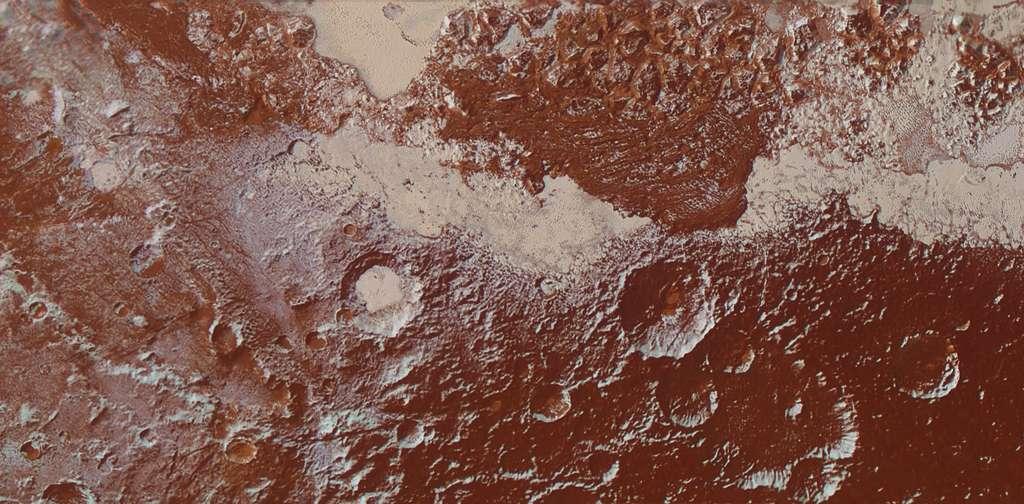Région de transition entre la plaine Spoutnik (en haut), piquée d'une multitude de puits de sublimation et les reliefs plus anciens, en direction de Cthulhu, couverts de Tholins et où l'où compte de nombreux cratères. © Nasa, JHUAPL, SwRI