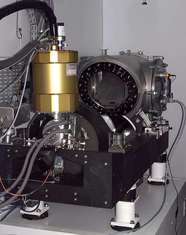 Le spectrographe Sophie, sur ses quatre pieds antivibrations. Il reçoit la lumière du télescope par quatre fibres optiques (grises, en haut à gauche). La lumière est envoyée à travers le hublot (une lame de Schmidt, au centre). © OAMP