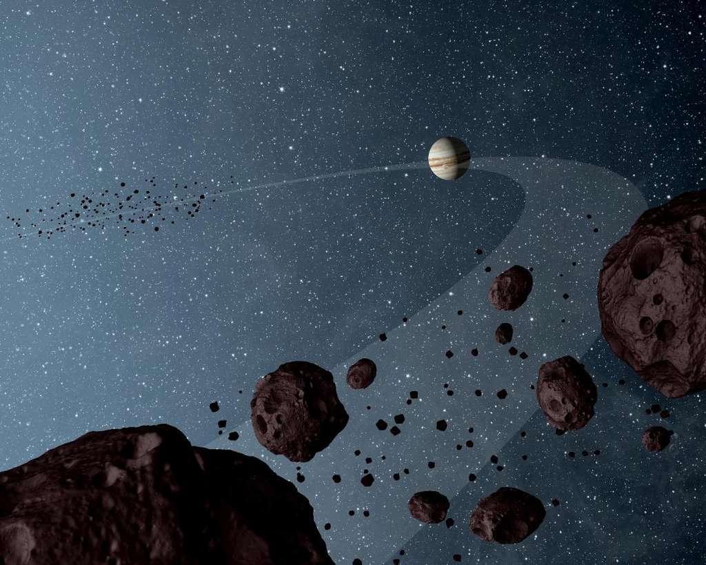 À 60° de part et d'autre de Jupiter, sur son orbite, les champs de gravité combinés du Soleil et de la géante piègent des petits corps célestes qui accompagnent alors Jupiter. Ce sont les troyens, qu'illustre ce dessin d'artiste. © Nasa