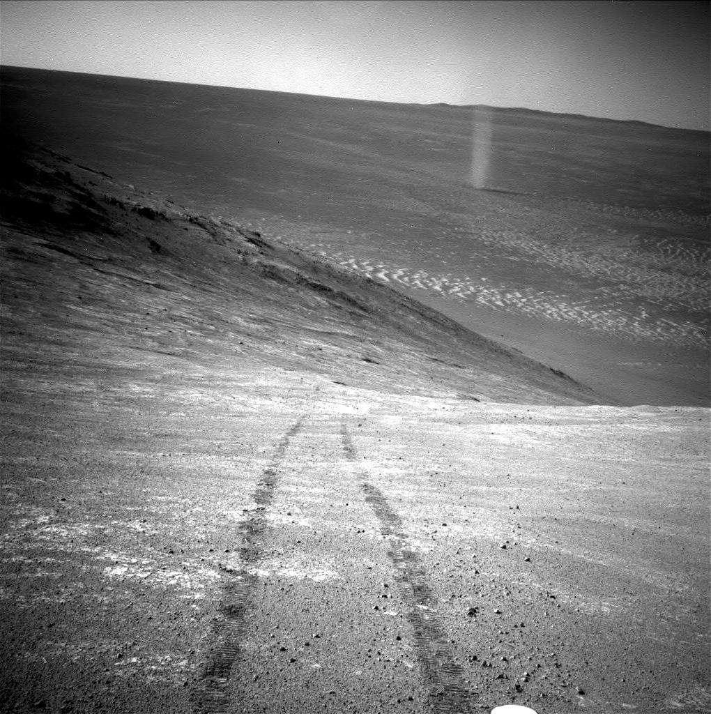 « Démon de poussière » à l'intérieur du grand cratère d'impact Endeavour (22 km de diamètre) photographié par la NavCam d'Opportunity lors 4.332e jour sur Mars. Le rover se roule sur le flanc sud de la vallée de Marathon qui coupe d'est en ouest le bord du cratère. Derrière le tourbillon, apparaît la crête du bord opposé. © Nasa, JPL-Caltech