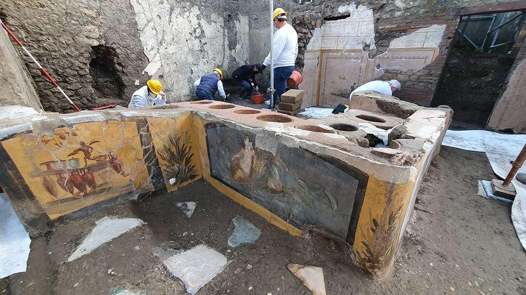 Vue d'ensemble du thermopolium complètement excavé à Pompéi. On voit la fresque représentant la néréide et celle de l'homme portant des charges. © Site historique de Pompéi