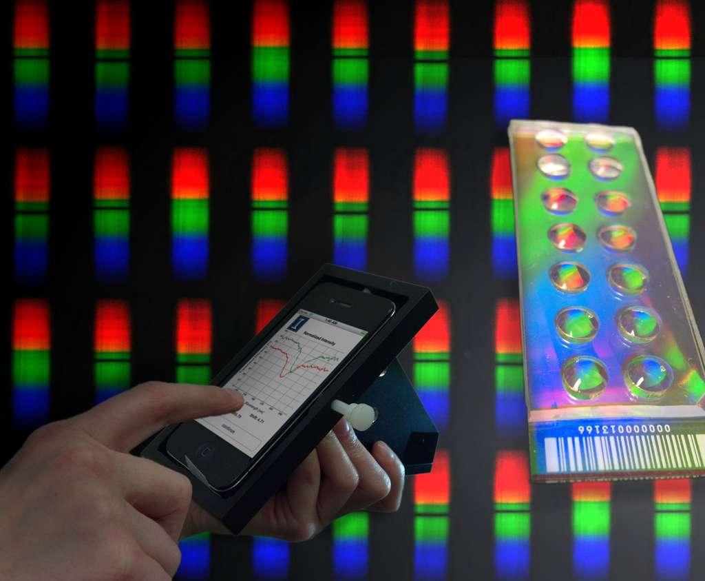 La station d'accueil pour iPhone conçue par l'équipe de l'université de l'Illinois se compose d'une série de lentilles et de filtres optiques. Elle maintient le smartphone sous un certain angle afin d'exploiter les capacités de son capteur photo. Pour réaliser une analyse, on insère la lame microscopique dans la fente prévue à cet effet. Depuis l'iPhone, on lance l'application dédiée qui active le capteur photo. C'est en mesurant le degré de changement dans la longueur d'onde réfléchie par le cristal photonique se trouvant dans la station d'accueil, que l'application peut produire un spectre. © Université de l'Illinois