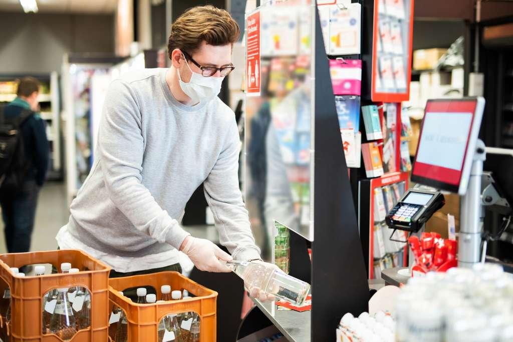 Un employé de la grande distribution équipé d'un masque et de gants. © Wellnhofer Designs, Adobe Stock