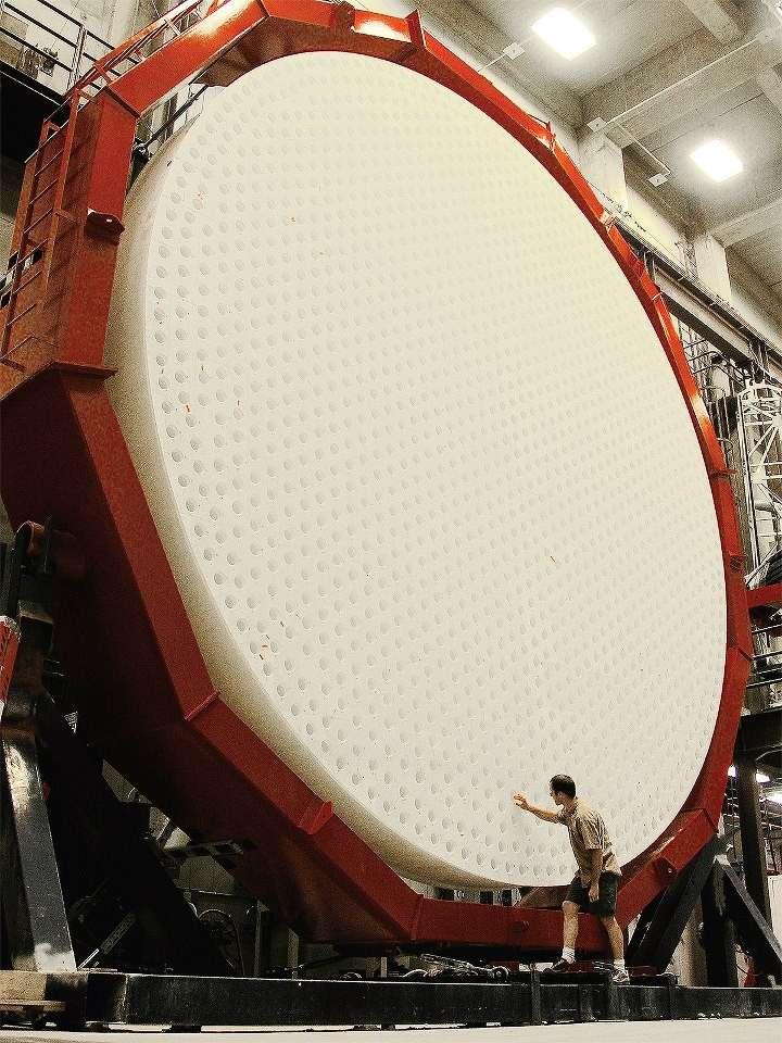 Inspection de l'arrière d'un miroir primaire de 8,4 m de diamètre. Pour alléger le miroir, il a été coulé dans un moule en nid d'abeille, les alvéoles étant occupées par des briques réfractaires qui ont été enlevées après le refroidissement du miroir. © University of Arizona