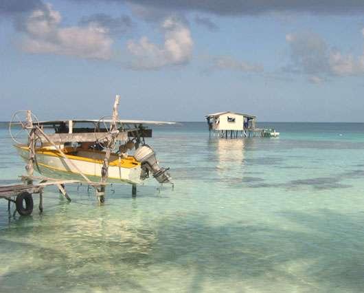 À gauche, un bateau et, à droite, au second plan, le « fare greffe », ce petit bâtiment souvent sur pilotis où les greffeurs réalisent les greffes. © Service de la perliculture, tous droits de reproduction interdits