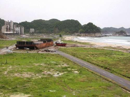 """Plage de Lhok Nga lors de la deuxième mission """"Tsunarisque"""" en Août 2005. 300 mètres de plage avaient été dévastés lors du tsunami du 26 décembre 2004, on voit la barge de la cimenterie et au fond la cimenterie Lafarge. La végétation a recouvert assez vite le sable répandu par le tsunami dans les terres. """"Tsunarisque"""" est un projet scientifique sur deux ans. Ce programme a effectué depuis Janvier 2005 trois missions sur le terrain, l'une d'urgence en Janvier/Février, la deuxième en août puis la dernière, en décembre 2005, mobilisant à chaque fois une petite trentaine de chercheurs français et indonésiens. Une dernière suivra, pour sonder et explorer les fonds marins proches des côtes au premier semestre 2006. © CNRS Photothèque / PARIS Raphaël."""