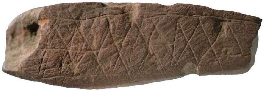 Ocre gravé daté de 75.000 ans, trouvé dans la grotte de Blombos en Afrique du Sud. Le morceau d'ocre mesure environ 8 cm de large. Les symétries miroir et par translation spatiale, clairement identifiables, laissent penser qu'il s'agit de la plus ancienne trace de pensée symbolique que nous possédons actuellement, à moins qu'il ne s'agisse d'un exercice ludique ou purement esthétique (œuvre d'art). © Francesco d'Errico, Journal of Human Evolution, 2009