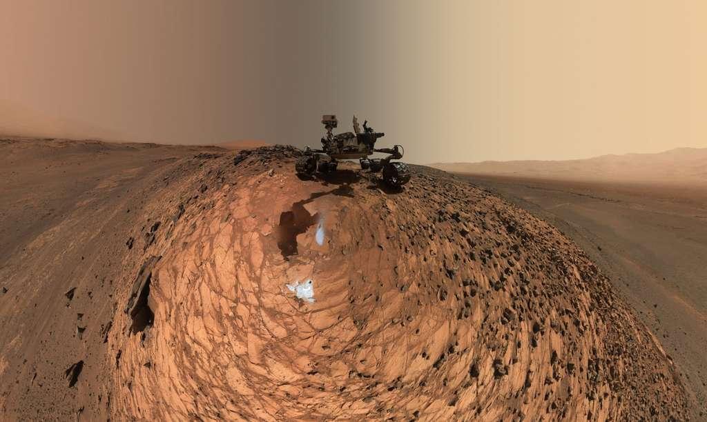 Image composite de 92 photos individuelles prises le 5 août 2015 avec la caméra Mahli, installée au bout du bras articulé. Le rover est juché sur une petite colline, où il a foré deux trous (les taches grises). Derrière lui, le mont Sharp, à gauche, et, à droite une partie des remparts ouest du cratère Gale. L'image en très haute résolution est téléchargeable ici (2,23 Mo). © Nasa, JPL-Caltech, MSSS