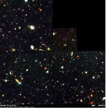 Figure 5 : le champ profond du télescope spatial Hubble. Dans cette petite zone du ciel soigneusement choisie pour ne pas contenir d'étoiles brillantes (on en voit qui ont une forme … d'étoiles), il a été possible de détecter 1500 galaxies dont certaines se trouvent à plus de 10 milliards d'années-lumière de la Terre.