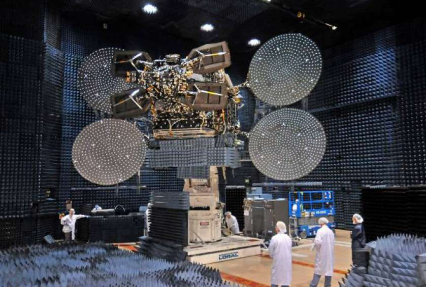 Le satellite EchoStar XVII installé dans une chambre anéchoïque (dont les parois absorbent fortement les ondes sonores) pour vérifier ses performances en radiofréquences et sa compatibilité électromagnétique. © Hughes