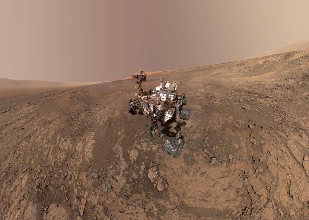 Curiosity sur le site Vera Rubin, le 23 janvier 2018 (sol 1943). Des dizaines d'images assemblées composent ce nouveau selfie. Juste derrière le rover, le site qu'il va bientôt explorer. Tout au fond : le sommet du mont Sharp. Téléchargez l'image en haute résolution ici. © Nasa, JPL-Caltech, MSSS