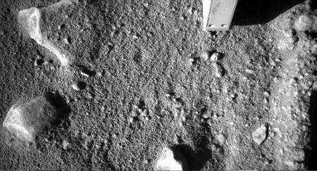 En haut à droite, l'extrémité du bras robotisé portant la pelle et diverses sondes est visible, partiellement enterrée. Crédit Nasa