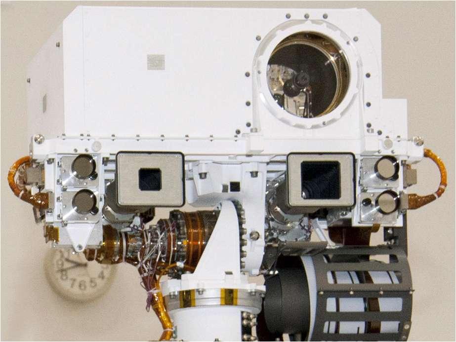 En haut du mât de Curiosity, l'instrument ChemCam (la boîte blanche avec la grosse lentille) envoie un laser pulsé sur une cible tandis que le capteur, derrière l'objectif, filme le nuage de plasma lumineux produit par cet échauffement. Un spectromètre analyse ensuite l'émission de cette lueur pour déterminer les composants présents dans la roche. On remarque les objectifs à ouverture carrée des deux caméras de mât, avec une focale longue à gauche et courte à droite. © Nasa, JPL-CalTech