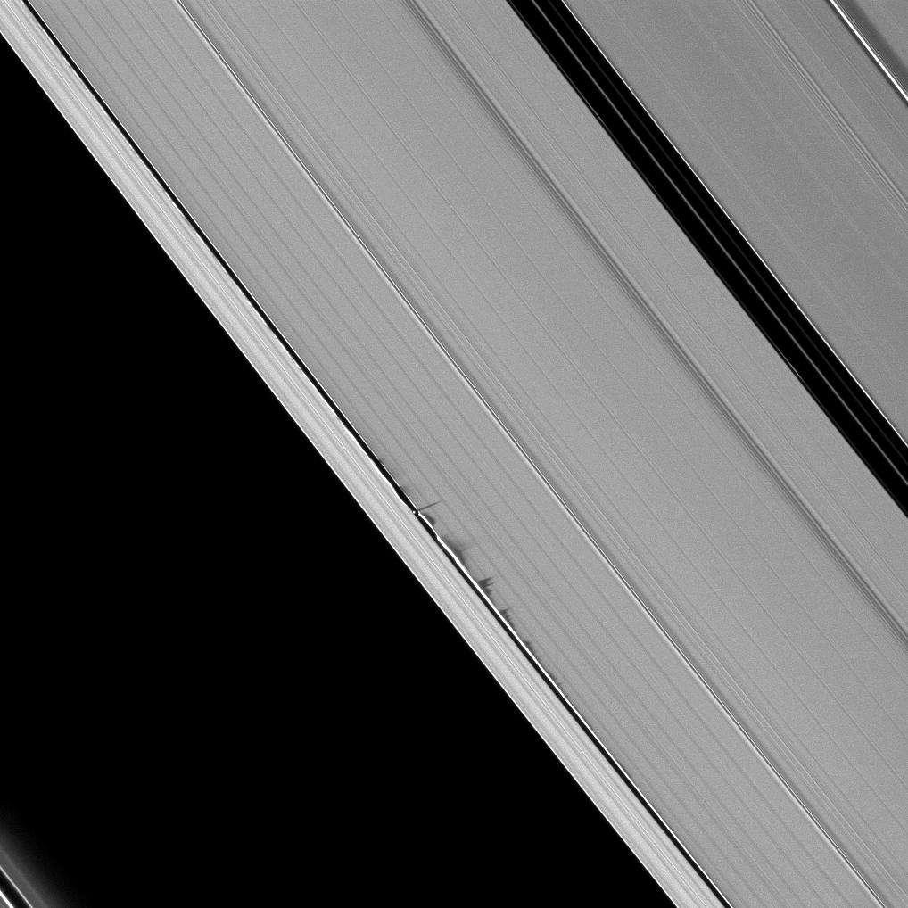 Sur cette image spectaculaire prise par la sonde Cassini, on voit des ondulations dans la structure des anneaux de Saturne, créées par le passage de la petite lune Daphnis. Les perturbations gravitationnelles ont déformé localement les anneaux en provoquant une remontée des matériaux au-dessus du plan des anneaux. On voit même l'ombre que projettent ces remontées. © N.A.S.A, JPL