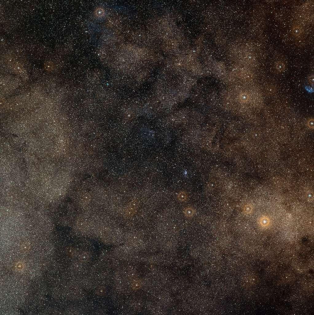 Cette image montre dans le domaine visible un champ d'environ 2,9 degrés entourant l'hypergéante jaune Iras 17163-3907. Elle a été prise à travers des filtres bleu, rouge et infrarouge dans le cadre de la campagne d'observation du Digitized Sky Survey 2. Elle se trouve au centre de l'image, noyée dans cette région de la Voie lactée riche en étoiles. En haut à gauche du centre on peut voir aussi une nébuleuse planétaire en forme d'anneau bleuté, il s'agit de NGC 6337. © ESO and Digitized Sky Survey 2