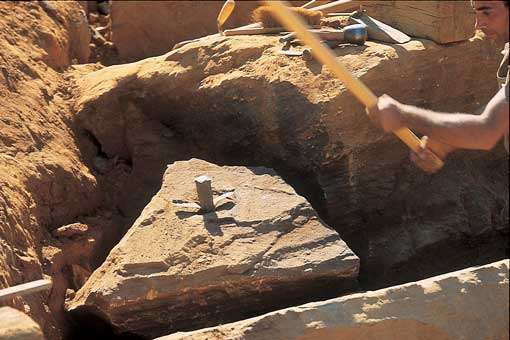 Extraction d'un bloc de pierre avec un coin et la masse. La pierre utilisée pour la construction du château est du grès ferrugineux. © Guédelon - Reproduction et utilisation interdites - Tous droits réservés