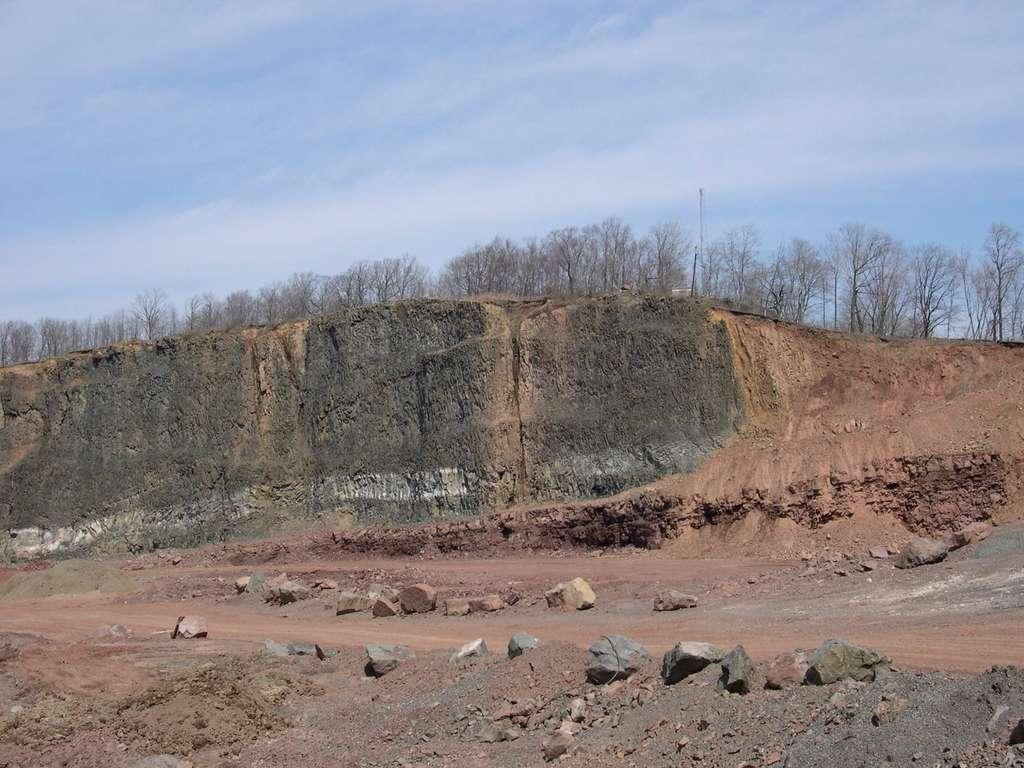 Cet affleurement peut être observé dans le New Jersey, aux États-Unis, à proximité d'habitations. Les roches noires à gauche sont des basaltes émis durant la formation de la province magmatique centre atlantique. Elles recouvrent des sédiments riches en organismes du Trias (en rouge). © Paul Olsen, Lamont-Doherty Earth Observatory