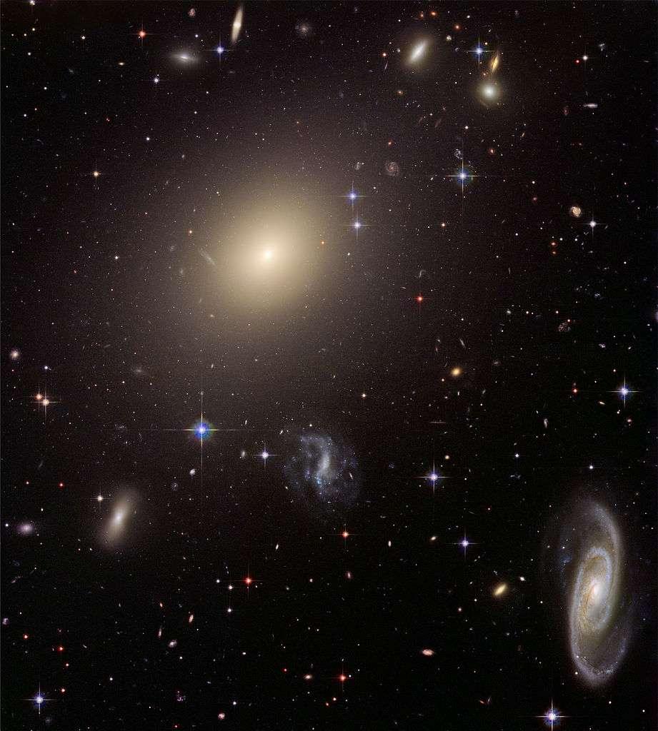 Abell S0470 est un amas de galaxies situé dans la constellation du Centaure, à environ 465 millions d'années-lumière (143 Mpc) de la Voie lactée. Il est dominé par ESO 325-G004, une galaxie elliptique géante dont la masse provoque un effet de lentille gravitationnelle sur les objets situés au loin à l'arrière-plan. ESO 325-G004 est un exemple typique de Brightest Cluster Galaxy. © Nasa, Esa