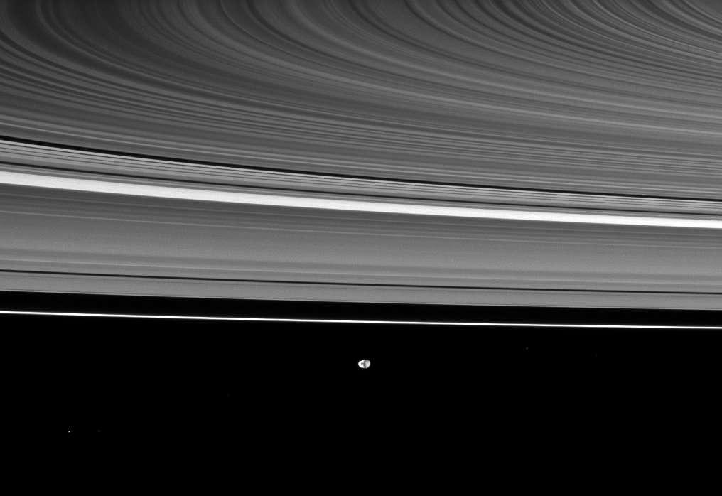 Les anneaux de saturne, vus par la sonde Cassini, avec, au loin, le petit Janus (179 kilomètres de diamètre, découvert en 1966 par Audouin Dollfus), à 2,1 millions de kilomètres de l'engin spatial. © Nasa/JPL/Space Science Institute