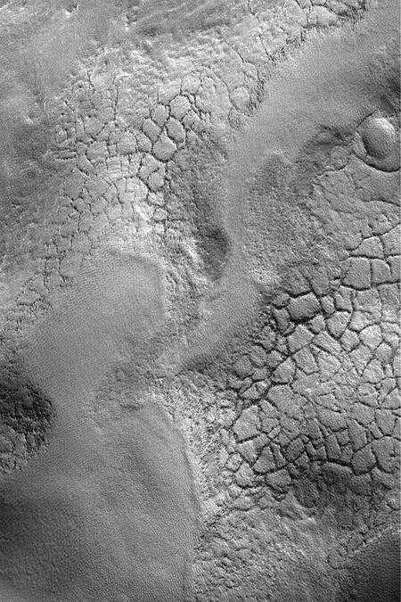 Succession de plaines craquelées et de vallées au fond du cratère Lyot. Image prise par Mars Reconnaissance Orbiter, d'une résolution de 30 mètres par pixel. Cliquer pour agrandir. Crédit Nasa