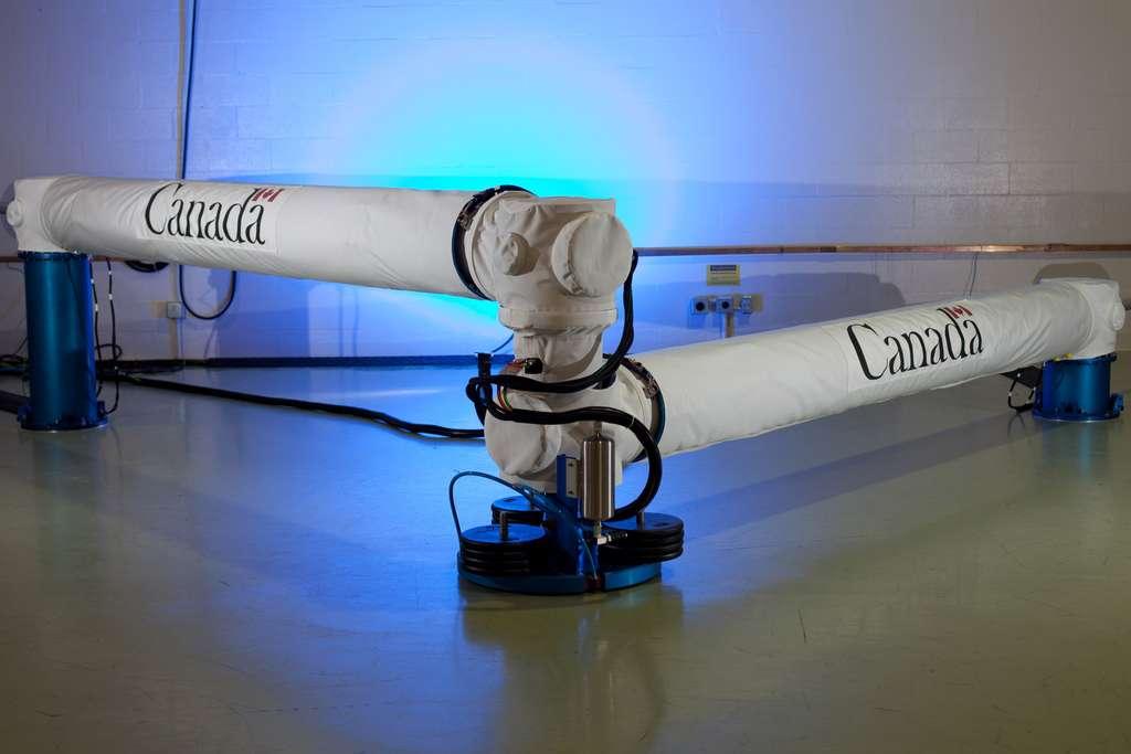 Prototype de bras robotique de même portée de 15 m que le Canadarm2 mais bien plus compact et allégé. Il est destiné aux engins spatiaux plus petits du futur. Conçu pour fonctionner comme banc d'essai sur Terre, le grand Canadarm de nouvelle génération repose sur des coussins d'air qui lui donnent une grande liberté de mouvement (six degrés de liberté). Il servira à simuler le déploiement du bras au cours de tâches exigeantes comme la capture et l'amarrage de gros satellites à des fins de ravitaillement. © Agence spatiale canadienne