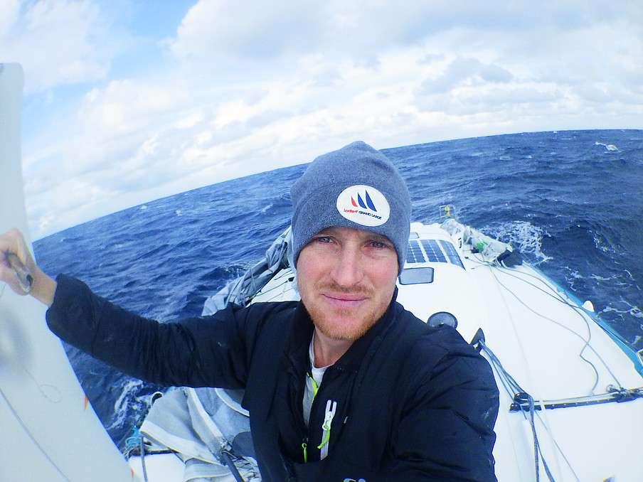 Conrad Colman, le 11 février, se prend en photo à l'avant du bateau. Derrière, il n'y a plus de mât. Sur le pont arrière, à droite sur l'image, la bôme est arrimée et pourra servir à fabriquer un grément de fortune. © Conrad Colman