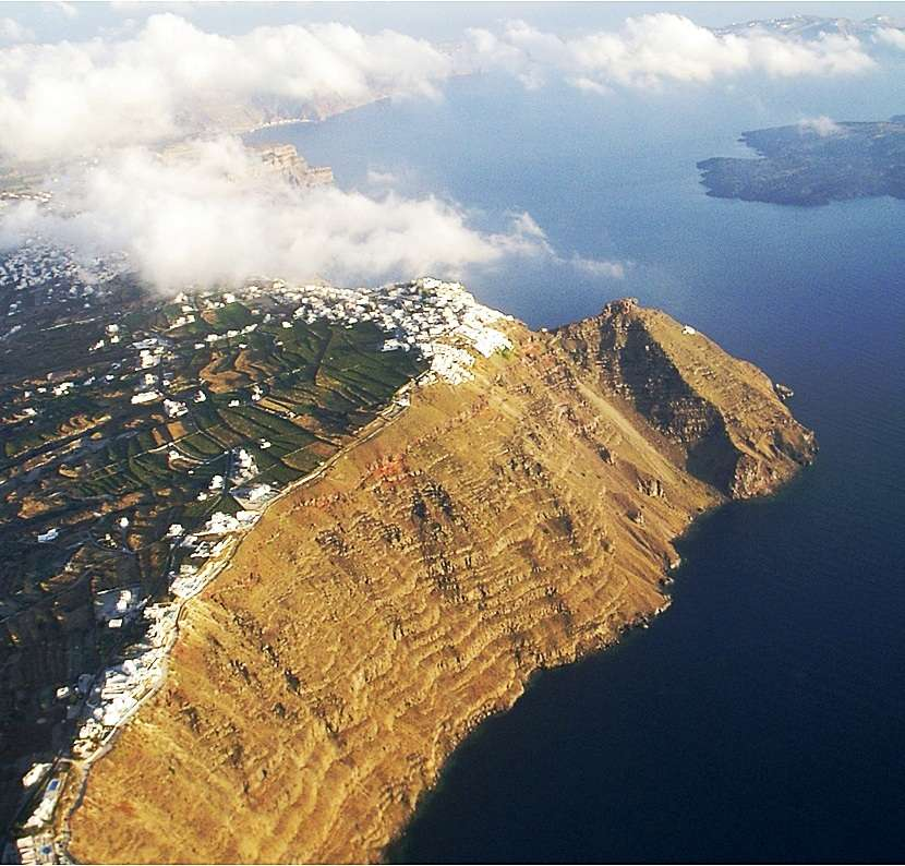 Vue aérienne de la falaise intérieure de la caldera de Santorin, avec ses couches de téphras caractéristiques et bien visibles. Une branche d'olivier trouvée sur cette falaise a été utilisée pour dater l'éruption minoenne. © Turi Humbel, WSL, université de Zurich
