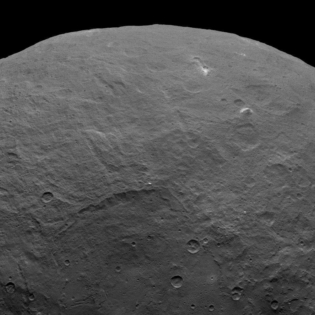 Sur cette image prise par Dawn le 6 juin 2015, à 4.400 km au-dessus de la surface de Cérès, on remarque plusieurs points brillants et aussi la présence d'une montagne pyramidale aux pentes abruptes. Elle culmine à environ 5.000 mètres. © Nasa, JPL-Caltech, UCLA, MPS, DLR, IDA