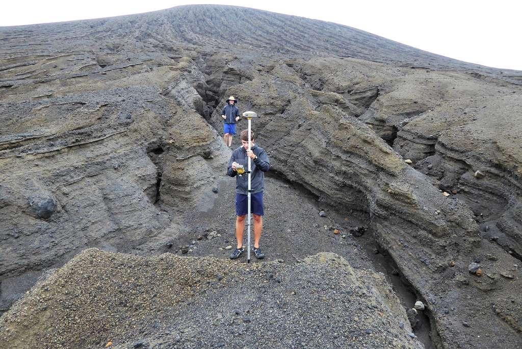 Un étudiant de la SEA effectue un relevé de position GPS au creux d'une des nombreuses ravines découpées par les précipitations sur les flancs du cône volcanique. Elles atteignent presque deux mètres de profondeur. © Dan Slayback